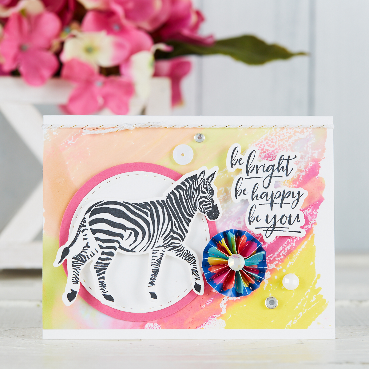 handmade card by Mariana Grigsby with zebra stamp from Escape the Ordinary Stamp Set from Fun Stampers Journey, with Gel Press watercolor background in pink, peach and yellow #funstampersjourney #cardmaking